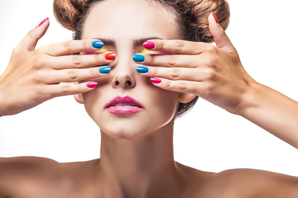 Model, a woman with bright makeup and bright nail Polish on a wh